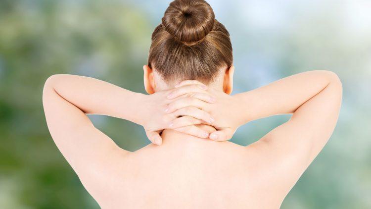 Frau fasst sich mit beiden Händen an Nacken