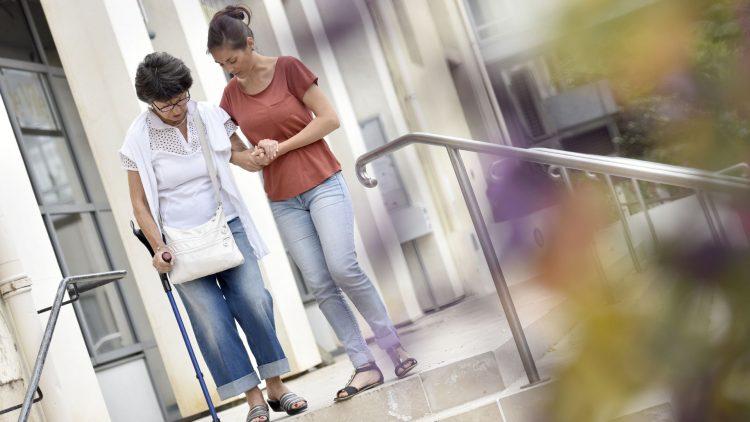Junge Frau stützt ältere Frau beim Treppenabsteigen