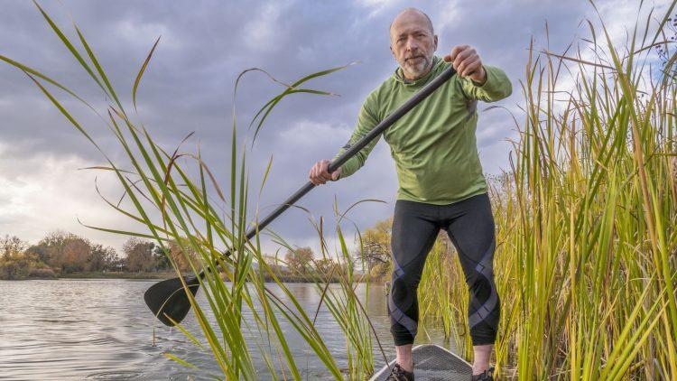 Mann steht auf einem Stand UP Paddle Surfboard