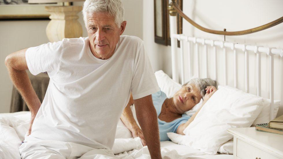 Mann steht mit Schmerzen aus dem Bett auf