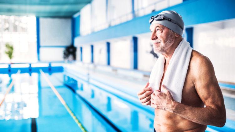 Mann am Beckenrand im Schwimmbad