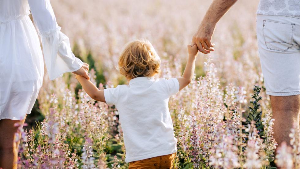 Kleines Kind an der Hand der Eltern