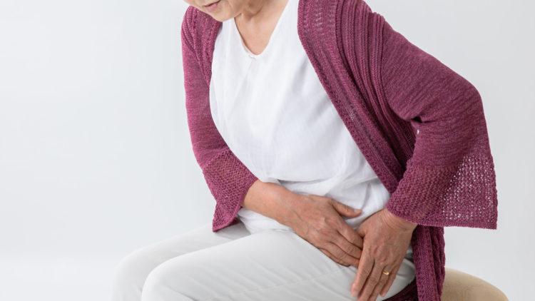 Frau hält sich die Hüfte wegen Arthroseschmerzen