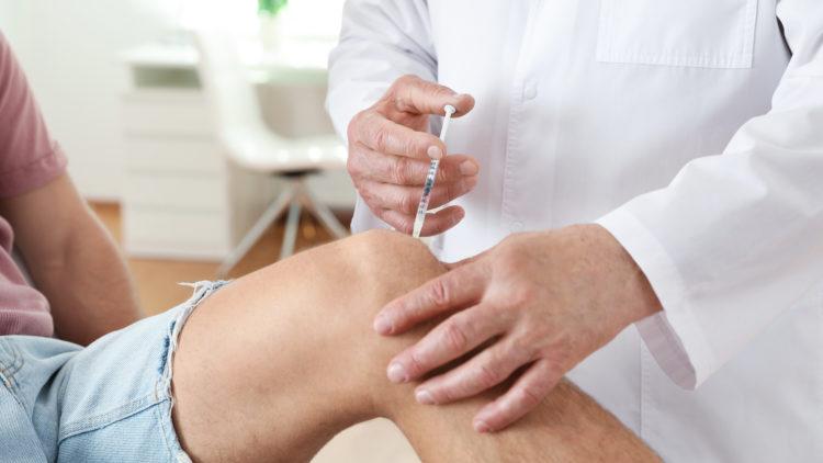 Arzt verabreicht einem Patienten mit Knieschmerzen eine Spritze